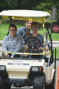 Student participates in the event by driving a golf cart using the goggles. He has a passenger in the cart that is recording him.