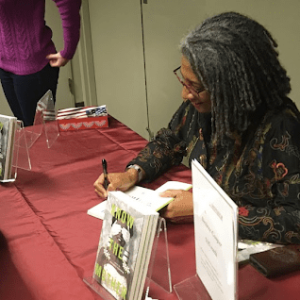 Desiree Cooper signs a book for a student.