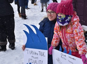women and child participate at march holding signs